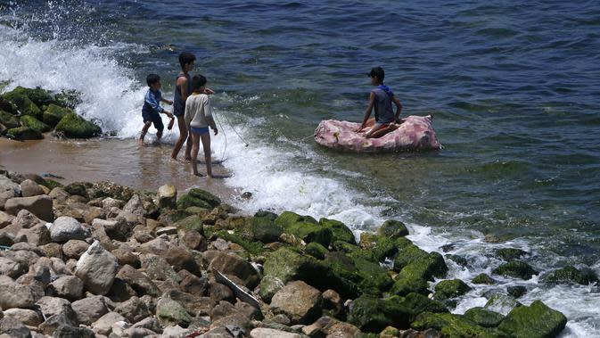 Anak-anak bermain air selama bulan suci Ramadan di pantai Kota Gaza, Palestina, Jumat (1/5/2020). (MOHAMMED ABED/AFP)