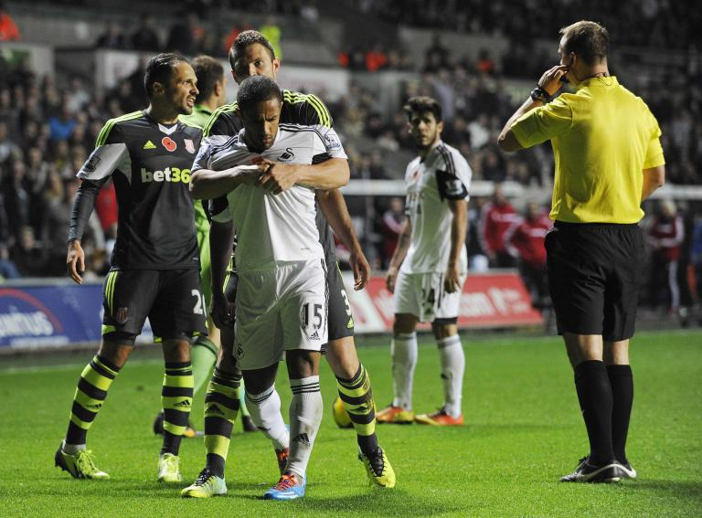 Swansea City's Wayne Routledge is restrained by Stoke City's Erik Pieters during English Premier League in Wales
