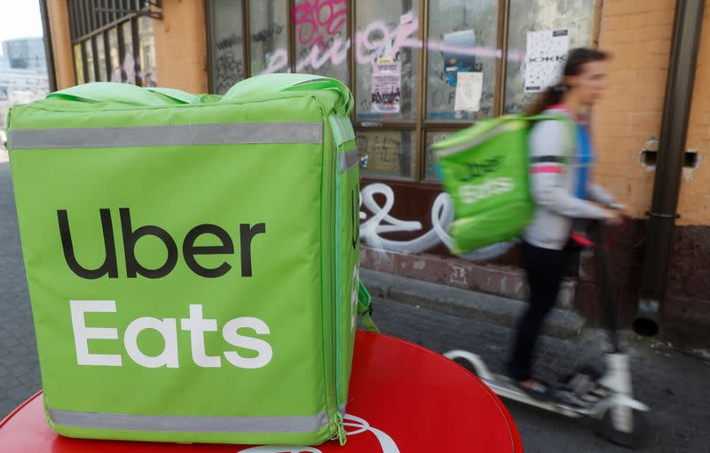 An Uber Eats courier rides a scooter in Kiev