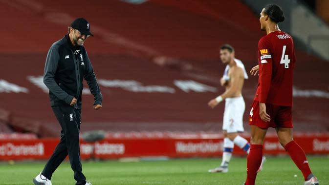 Pelatih Liverpool, Jurgen Klopp merayakan kemenangan dengan bek Virgil van Dijk setelah pertandingan melawan Crystal Palace pada lanjutan Liga Inggris di di Stadion Anfield di Liverpool, Inggris (24/6/2020). Liverpool menang telak 4-0 atas Crystal Palace. (Phil Noble/Pool via AP)
