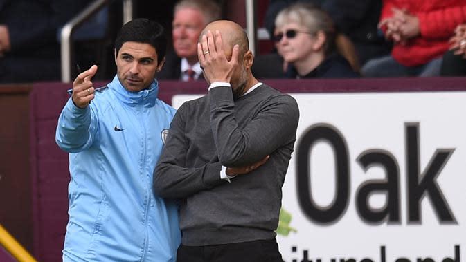 Pelatih Manchester City Pep Guardiola (kanan) menutup wajahnya saat berbincang dengan asistennya Mikel Arteta pada pertandingan Burnley kontra Manchester City di Turf Moor, Burnley, Inggris, 28 April 2019. Arsenal dikabarkan akan segera meresmikan Arteta sebagai pelatih baru. (Oli SCARFF/AFP)