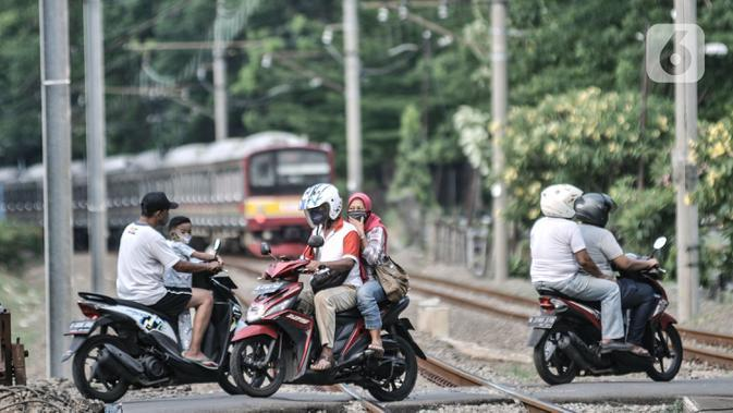 Pengendara motor saar melintasi perlintasan sebidang tanpa palang pintu di kawasan TPU Tanah Kusir, Jakarta, Kamis (17/9/2020). Sebelumnya pada Kamis (17/9) pagi tadi terjadi kecelakaan yang melibatkan sebuah mobil dan KRL di perlintasan tersebut. (merdeka.com/Iqbal S. Nugroho)