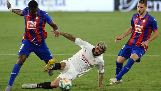 Gelandang Sevilla, Ever Banega, berebut bola dengan gelandang Eibar, Pape Diop, pada laga lanjutan La Liga pekan ke-34 di Estadio Ramon Sanchez Pizjuan, Selasa (7/7/2020) dini hari WIB. Sevilla menang 1-0 atas Eibar. (AFP/Cristina Quicler)