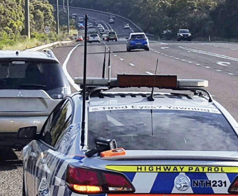 A Highway Patrol vehicle pulls over a car on a highway. Source: Traffic and Highway Patrol Command