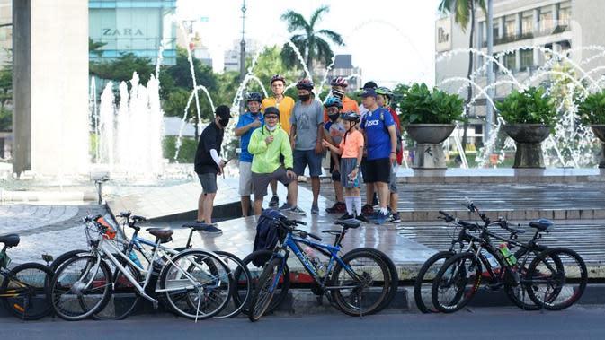 Sejumlah pesepeda berpose di kawasan Bundaran HI, Jakarta, Minggu (24/5/2020). Adanya PSBB serta Hari Raya Idul Fitri 1441 H dimanfaatkan sebagian warga untuk bersepeda di jalan protokol yang sepi dibanding hari biasa. (Liputan6.com/Immanuel Antonius)