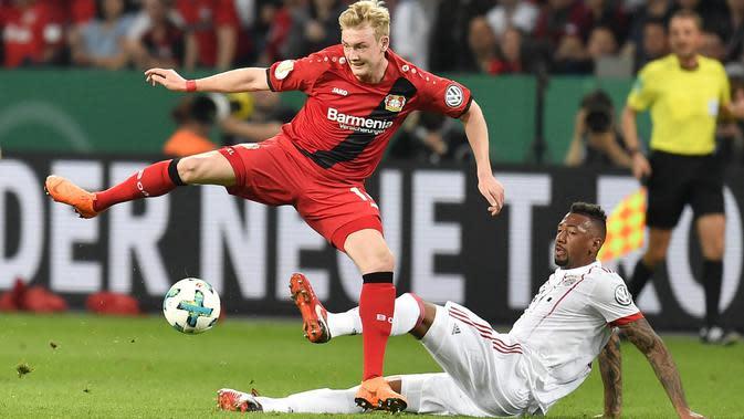 Bek Bayern Munchen, Jerome Boateng, berebut bola dengan gelandang Bayer Leverkusen, Julian Brandt, pada laga DFB Pokal di Stadion BayArena, Selasa (17/4/2018). Bayern Munchen menang 6-2 atas Bayer Leverkusen. (AP/Martin Meissner)