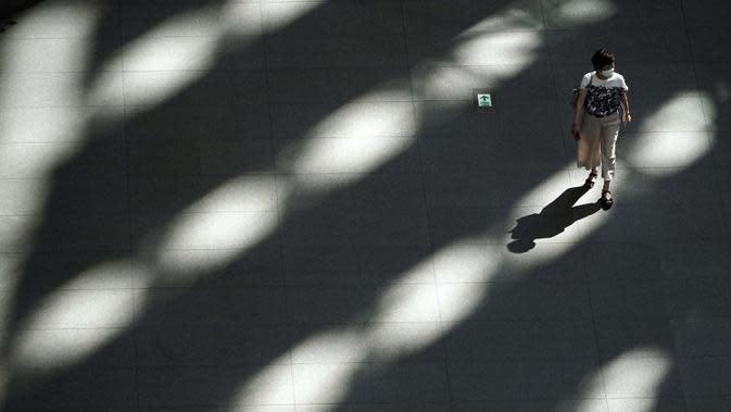 Seorang wanita yang mengenakan masker untuk membantu mengekang penyebaran virus corona COVID-19 berjalan di bawah naungan sebuah gedung di Tokyo, Jepang, 4 September 2020. Tokyo mengonfirmasi lebih dari 130 kasus COVID-19 pada 4 September 2020. (AP Photo/Eugene Hoshiko)