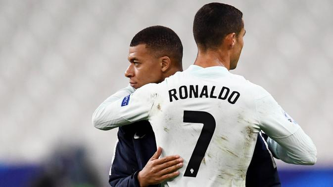 Striker Portugal, Cristiano Ronaldo, berpelukan dengan striker Prancis, Kylian Mbappe, usai laga UEFA Nations League di Stadion Stade de France, Senin (12/10/2020). Kedua tim bermain imbang 0-0. (AFP/Franck Fife)