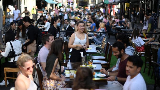 Pramusaji menerima pesanan pelanggan di meja di luar restoran di Soho, London, saat pemerintah Inggris mempertimbangkan pembatasan baru pada Minggu (20/9/2020). Inggris kemungkinan akan kembali memberlakukan tindakan lockdown akibat lonjakan tajam infeksi corona COVID-19. (DANIEL LEAL-OLIVAS/AFP)