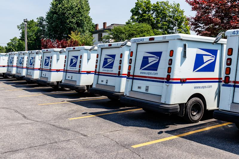 Photo shows United States Postal Service vans parked.