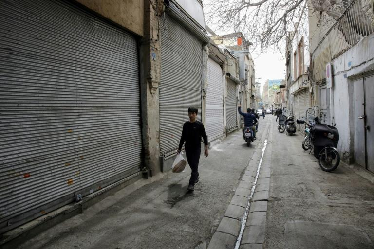 An Iranian youth walks past closed shops in the capital Tehran's grand bazaar