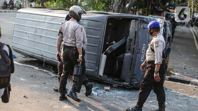Sejumlah polisi melihat sebuah mobil polisi yang dirusak massa saat bentrok di kawasan Pejompongan, Jakarta, Rabu (7/10/2020). (Liputan6.com/Faizal Fanani)