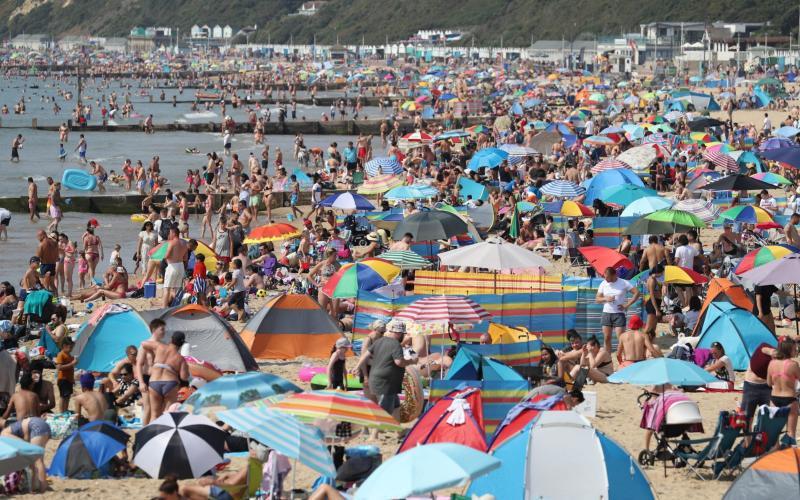 Sunbathers on Bournemouth beach in Dorset - PA