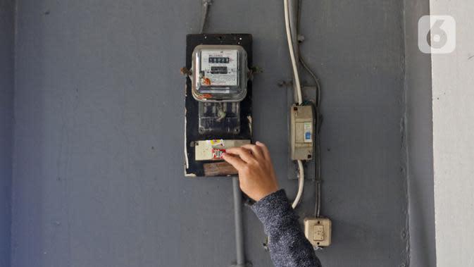 Warga memeriksa meteran listrik di kawasan Matraman, Jakarta, Kamis (2/4/2020). Di tengah pandemi COVID-19, pemerintah menggratiskan biaya tarif listrik bagi konsumen 450 Volt Ampere (VA) dan pemberian keringanan tagihan 50 persen kepada konsumen bersubsidi 900 VA. (Liputan6.com/Herman Zakharia)
