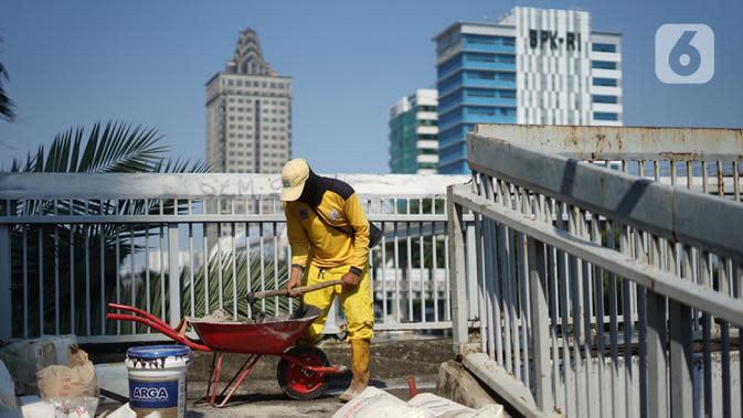 Petugas Bina Marga memerbaiki lantai Jembatan Penyeberangan Orang (JPO) yang berlubang di kawasan Tebet, Jakarta, Kamis (27/8/2020). Perbaikan dilakukan guna meningkatkan kenyamanan bagi pejalan kaki yang melintas. (Liputan6.com/Immanuel Antonius)