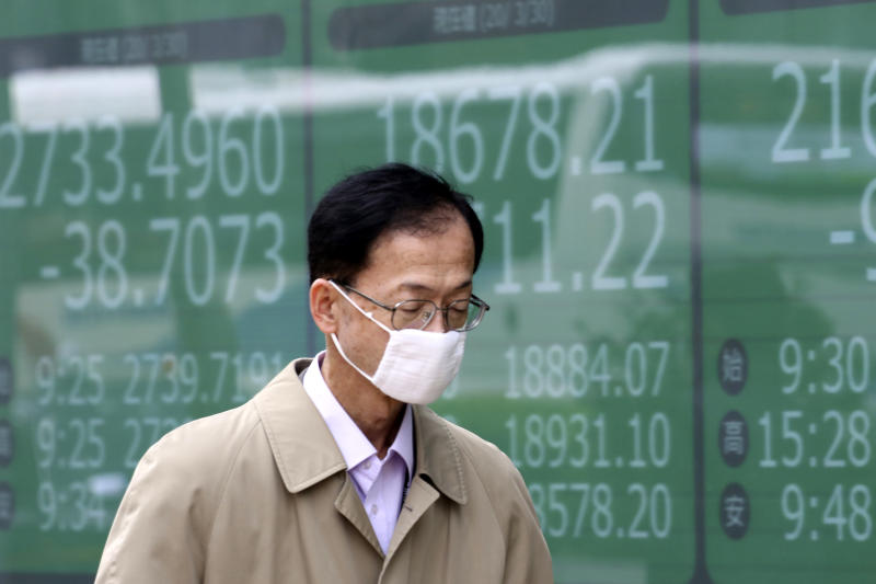A man walks by an electronic stock board of a securities firm in Tokyo, Monday, March 30, 2020. Asian shares started the week with further losses as countries reported surging numbers of infections from the coronavirus that has prompted shutdowns of travel and business in many parts of the world.(AP Photo/Koji Sasahara)