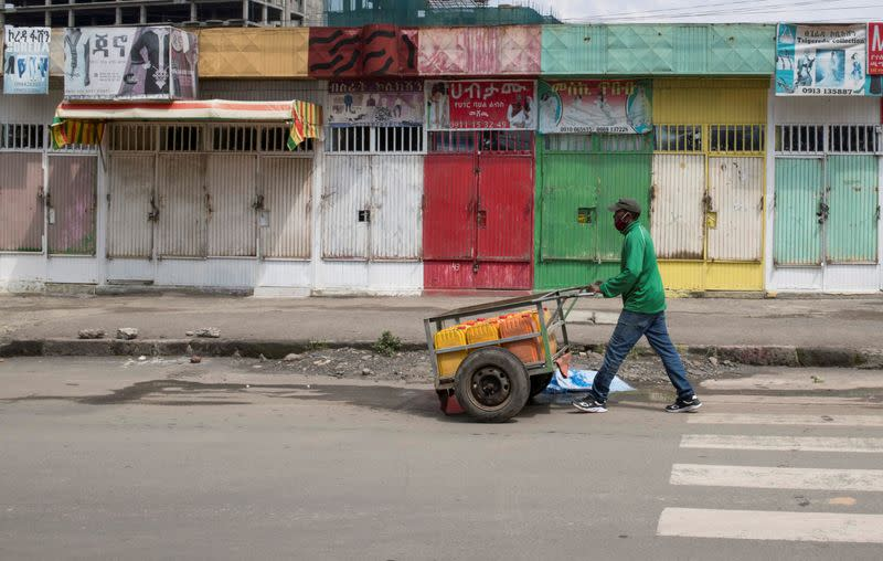 A man pushes a hand-cart past closed shops following protests in Addis Ababa