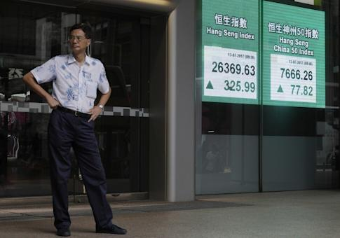 A man stands next to a bank electronic board showing the Hang Seng Index rally outside the Hong Kong stock exchange building. A large number of employees covered by the Mandatory Provident Fund invests in Hong Kong stock funds. Photo: AP