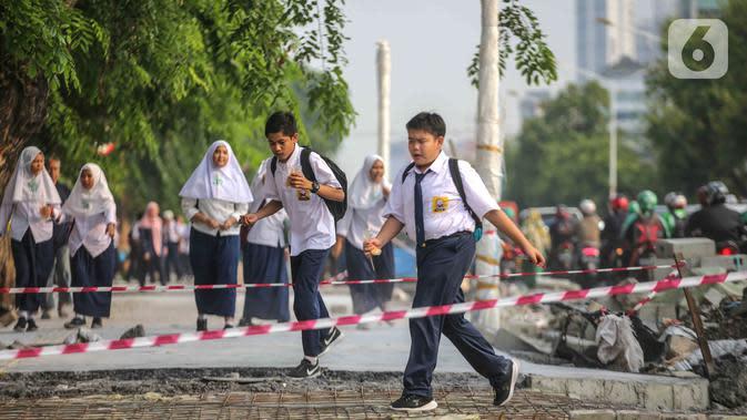 Pelajar melintasi trotoar yang sedang direvitalisasi di kawasan Kramat Raya, Jakarta, Rabu (6/11/2019). Revitalisasi trotoar menyebabkan para pejalan kaki harus berjalan di pinggir jalan dan bersinggungan dengan sepeda motor. (Liputan6.com/Faizal Fanani)
