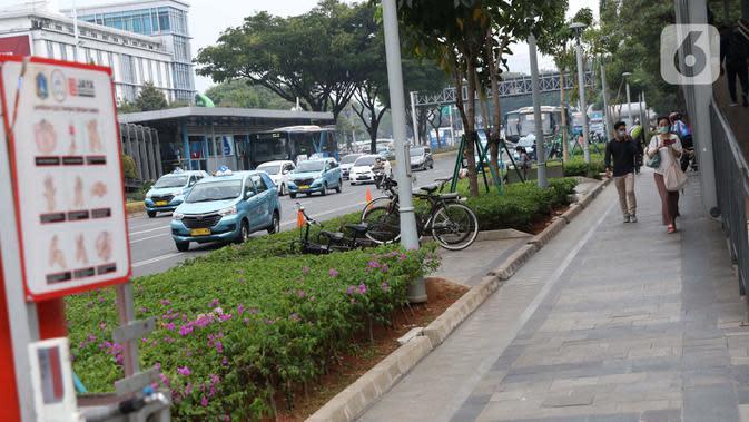 Warga menggunakan masker berjalan di pedestrian kawasan Jalan Jenderal Sudirman, Jakarta, Kamis (10/9/2020). Setelah mempertimbangkan sejumlah faktor, di antaranya ketersediaan tempat tidur rumah sakit, PSBB DKI Jakarta kembali diperketat per Senin (14/9). (Liputan6.com/Helmi Fithriansyah)