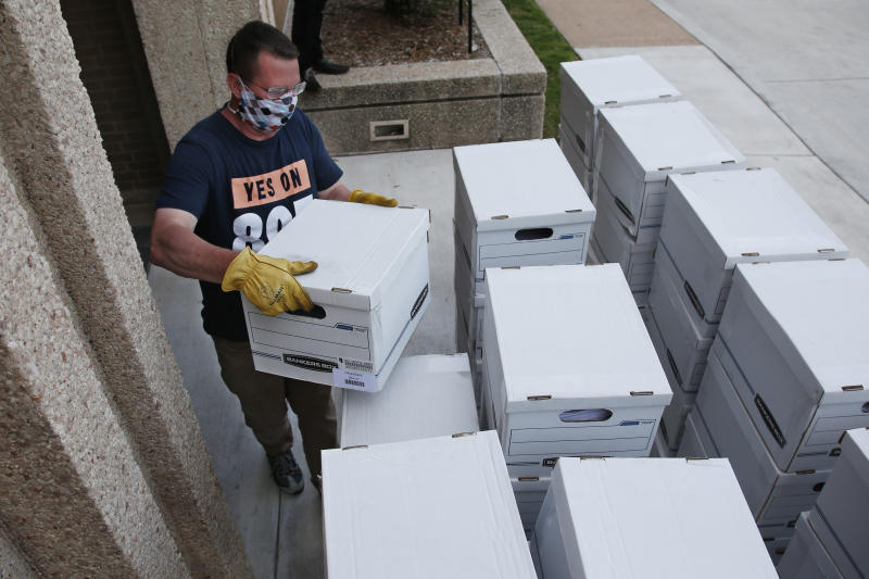 FILE - In this Monday, June 1, 2020 file photo, Kris Steele, Executive Director of OCJR and TEEM, carries a box of petitions as Yes on 805 delivers 260,000 gathered signatures to the Secretary of State's office in Oklahoma City, to put sentencing reform on a 2020 ballot. Oklahoma voters will vote in Tuesday's primary election on State Question 802, which would amend the Oklahoma Constitution to expand Medicaid health insurance. (AP Photo/Sue Ogrocki, Pool, File)