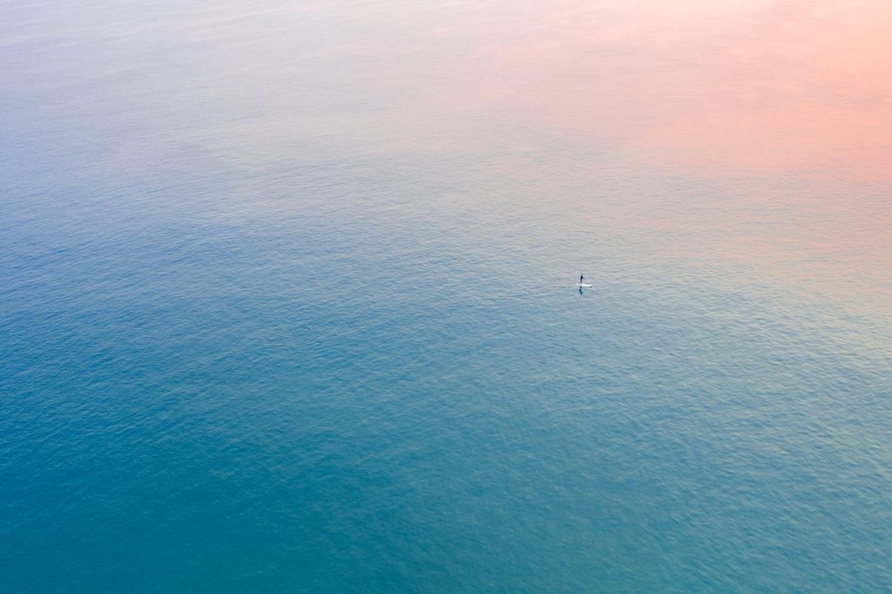 <p>Aerial view of a single surfer in Cabarita, Australia at sunrise. </p>