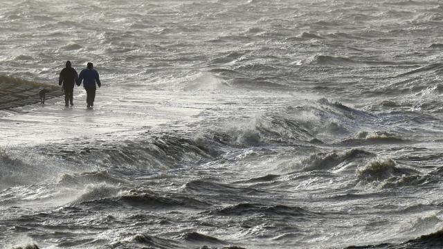 Passanten trotzen am Nordseedeich dem Sturm.
