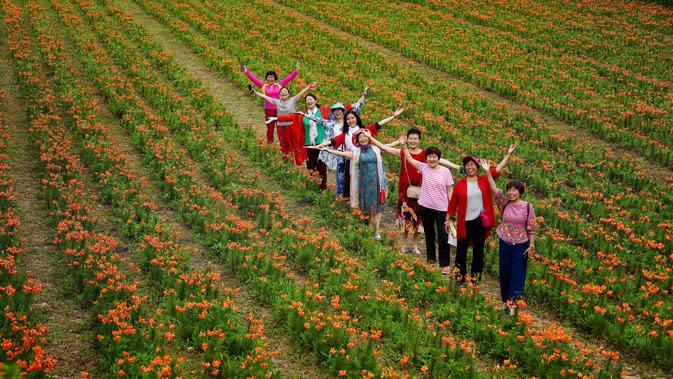 Orang-orang mengunjungi kebun bunga lili di Desa Baiyun, Wilayah Taibai, Provinsi Shaanxi, China barat laut (5/7/2020). Dalam beberapa tahun terakhir, dengan mempromosikan pariwisata pedesaan dan produk pertanian, desa ini telah mengangkat semua penduduknya keluar dari kemiskinan. (Xinhua/Liu Xiao)