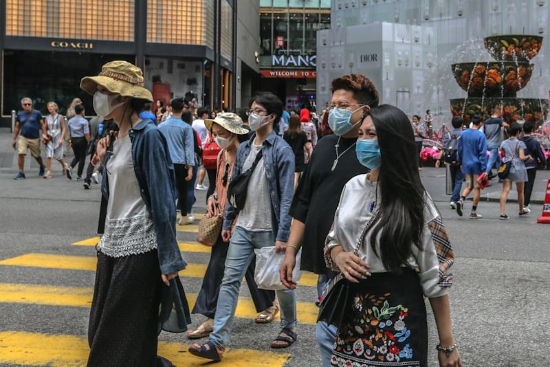People wearing face masks are pictured outside Pavilion Kuala Lumpur. — Picture by Firdaus Latif