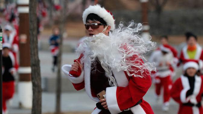 Seorang peserta yang mengenakan kostum Sinterklas mengikuti lomba lari maraton dalam acara Santa Run 2019 di Goyang, Korea Selatan, Sabtu (7/12/2019). Sekitar 2.000 peserta mengikuti lomba lari maraton sejauh 5 dan 10 kilometer. (AP Photo/Lee Jin-man)