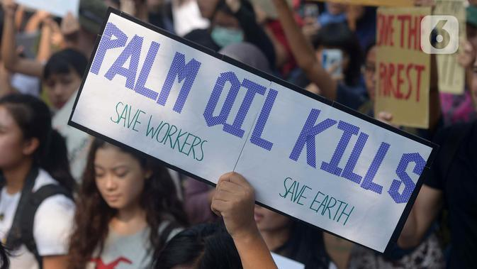 Spanduk bertuliskan 'Palm Oil Kills' serta 'Save Workers' dan 'Save Earth' ditunjukkan saat aktivis lingkungan hidup dari berbagai LSM berjalan kaki menuju Taman Aspirasi di Istana Merdeka, Jakarta, Jumat (29/11/2019). (merdeka.com/Imam Buhori)