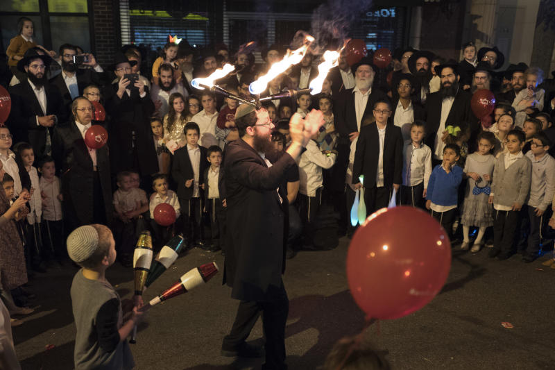 FILE - In this Oct. 18, 2016, file photo, a performer wears lighted sticks on his head while entertaining a crowd during the Jewish holiday of Sukkot, celebrated by the Chabad Lubavitch community in Brooklyn's Crown Heights neighborhood, in New York. For years, ultra-Orthodox Jewish families pushed out of increasingly expensive Brooklyn neighborhoods have been turning to the suburbs, where they have taken advantage of open space and cheaper housing to establish modern-day versions of the European shtetls where their ancestors lived for centuries before the Holocaust. (AP Photo/Mark Lennihan, File)