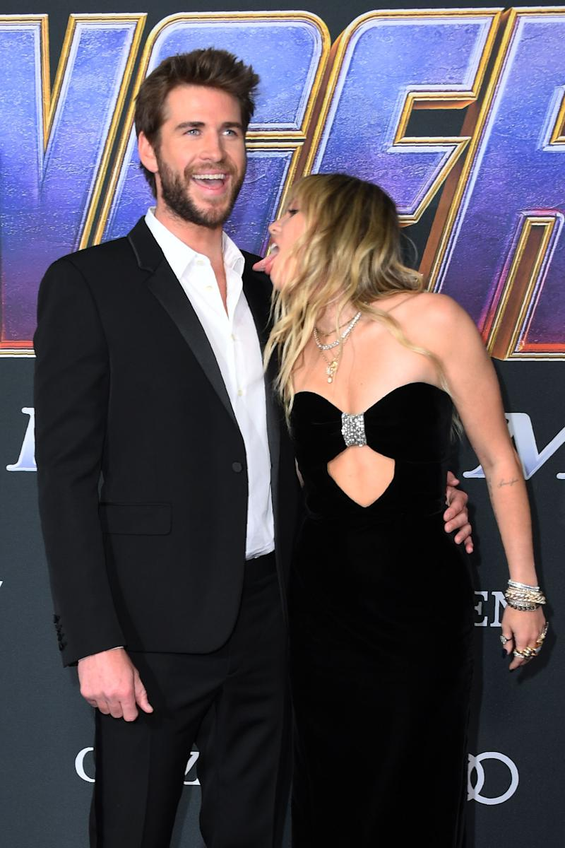 Liam Hemsworth laughs as Miley Cyrus licks him at the Endgame premiere