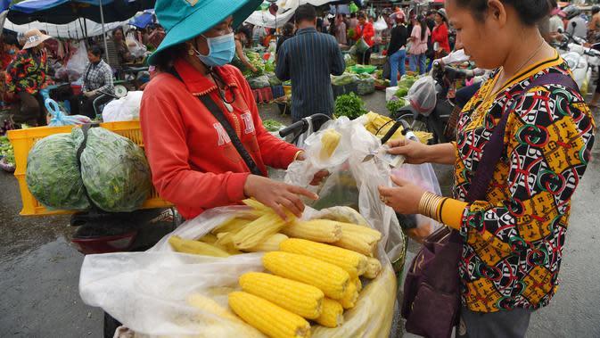 Seorang wanita membeli jagung rebus di sebuah pasar di Phnom Penh (24/7/2020). Pasar membentuk bagian integral dalam kehidupan orang Kamboja, dengan kunjungan harian yang dilakukan untuk persediaan makanan untuk hari itu serta barang-barang lainnya. (AFP/Tang Chhin Sothy)