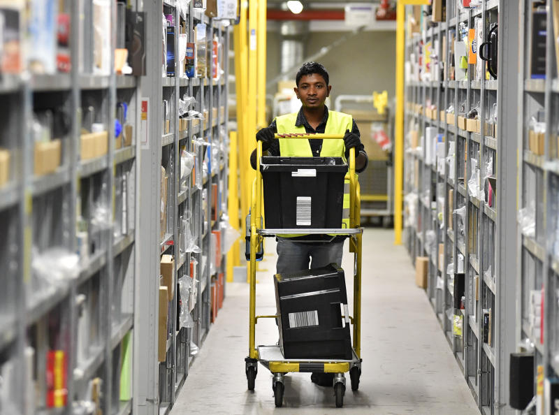 A worker collects goods for purchase orders at the giant storehouse of the Amazon Logistic Center in Rheinberg, Germany, Wednesday, Nov. 14, 2018. Amazon in Rheinberg hired extra workers for the Christmas sales. (AP Photo/Martin Meissner)