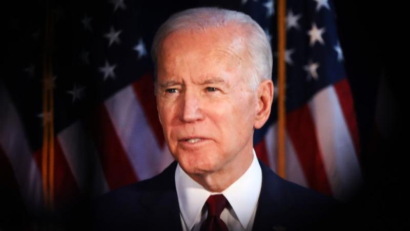Joe Biden in front of US flags.