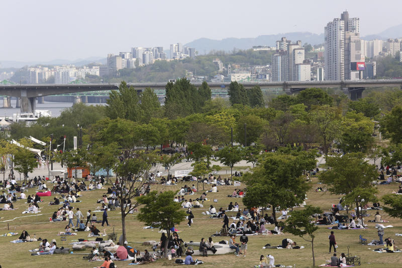 People enjoy at a public park on the Han River in Seoul, South Korea, Thursday, April 30, 2020. South Korean officials on Wednesday issued public pleas for vigilance to maintain hard-won gains against the coronavirus as the nation enters its longest holiday since infections surged in February. (AP Photo/Ahn Young-joon)