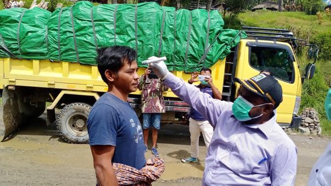 Wakil Bupati Tolikara melakukan pemeriksaan suhu tubuh kepada sopir yang masuk ke Tolikara. (Liputan6.com/Katharina Janur/Satgas Covid-19 Tolikara)