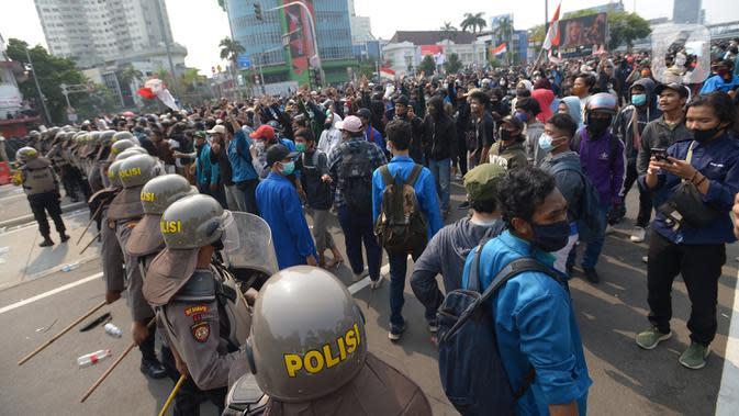 Aparat kepolisian menjaga massa aksi di kawasan Harmoni, Jakarta, Kamis (8/10/2020). Bentrokan pecah saat massa yang hendak menuju Istana Negara untuk menggelar unjuk rasa menolak UU Cipta Kerja diadang oleh aparat kepolisian. (merdeka.com/Imam Buhori)
