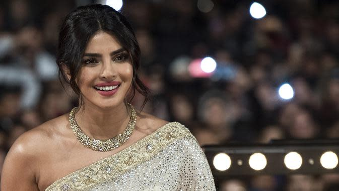 Aktris Priyanka Chopra tersenyum saat menghadiri Festival Film Internasional Marrakech ke-18 di Jemaa El Fnaa, Marrakech (5/12/2019). Priyanka Chopra tampil cantik memesona mengenakan busana sari emas dan brokat perak denga dengan kalung emas di lehernya. (AFP/Fadel Senna)
