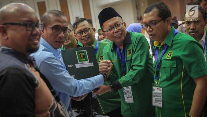 Sekjen PPP kubu Romahurmuziy (Romi) Arsul Sani menyerahkan berkas ke anggota Komisioner KPU, Hasyim Ashari di Kantor KPU RI, Jakarta, Sabtu (14/10). PPP kubu Romi mengantar berkas pendaftaran peserta Pemilihan Umum 2019. (Liputan6.com/Faizal Fanani)