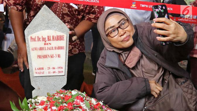 Seorang wanita berswafoto dengan latar belakang batu nisan Presiden ketiga BJ Habibie di Taman Makam Pahlawan Nasional Kalibata, Jakarta, Kamis (12/9/2019). Selain berdoa, tidak sedikit juga warga mengabadikan dengan kamera ponsel. (Liputan6.com/Herman Zakharia)