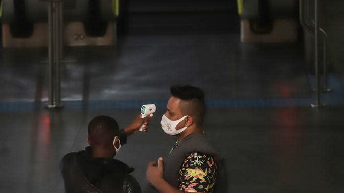 Seorang pria menjalani pemeriksaan suhu tubuh di stasiun kereta bawah tanah di Sao Paulo, Brasil (5/8/2020). Pengujian juga mengonfirmasi 57.152 infeksi baru, sehingga total kasus positif COVID-19 di negara tersebut menjadi 2.859.073, menurut Kementerian Kesehatan Brasil. (Xinhua/Rahel Patrasso)