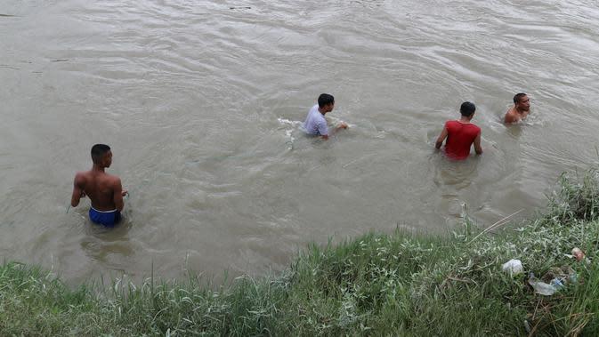 Puluhan warga menyelam untuk mencari keberadaan Riski (12 th) yang tenggelam di Sungai Palu. Sementara, sesekali buaya menampakkan diri di tengah sungai dan pinggiran, Minggu (12/1/2020). (Foto: Liputan6.com/Heri Susanto)