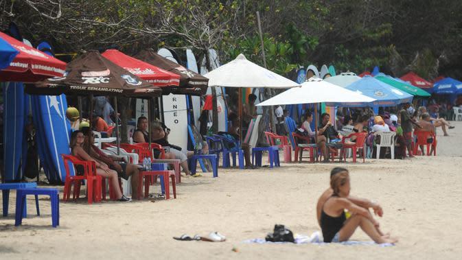 Sejumlah turis menikmati pantai Kuta di pulau pariwisata Indonesia di Bali (4/1). Pantai Kuta terkenal memiliki ombak yang bagus untuk olahraga selancar, terutama bagi peselancar pemula. (AFP Photo/Sony Tunbelaka)