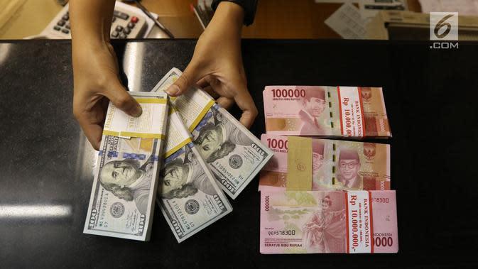 Pekerja menunjukan mata uang Rupiah dan Dolar AS di Jakarta, Rabu (19/6/2019). Nilai tukar rupiah terhadap dolar Amerika Serikat (AS) sore ini Rabu (19/6) ditutup menguat sebesar Rp 14.269 per dolar AS atau menguat 56,0 poin (0,39 persen) dari penutupan sebelumnya. (Liputan6.com/Angga Yuniar )