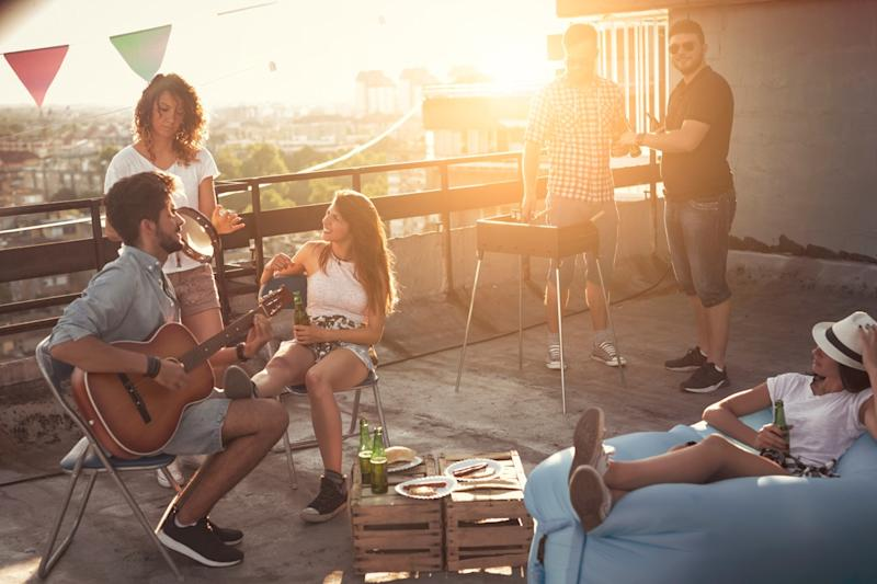 guy playing a guitar at a party on a roof