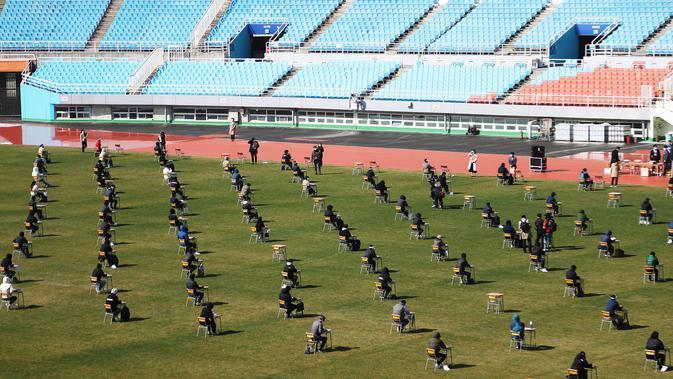 Pelamar kerja saat mengikuti ujian tertulis selama tes rekrutmen untuk Ansan Urban Corporation di stadion Wa di Ansan, Korea Selatan (4/8/2020). Pelamar juga harus memakai masker wajah dan memeriksa suhunya. (AFP/YONHAP)