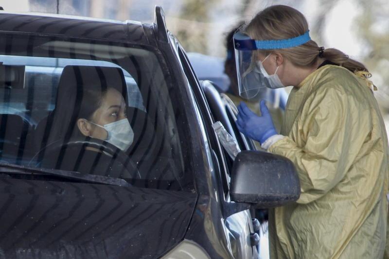 An Alberta Health Services employee speaks with a motorist at a drive-thru coronavirus testing facility in Calgary, Alberta, Friday, March 27, 2020. (Jeff McIntosh/The Canadian Press via AP)