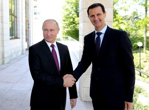 Russian President Vladimir Putin (L) shakes hands with his Syrian counterpart Bashar al-Assad during their meeting in Sochi on May 17, 2018